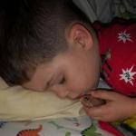 Niño duerme con un pescado.