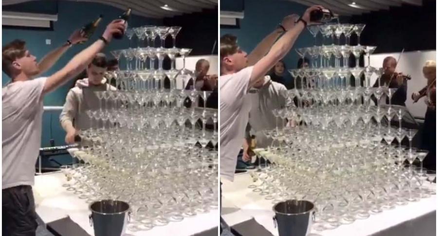 Barman sirve champaña en torre de copas.