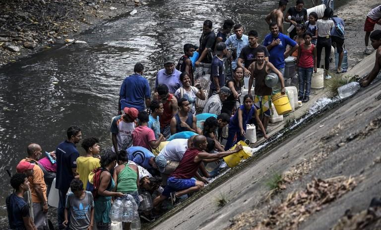 Venezolanos recogen agua de río contaminado