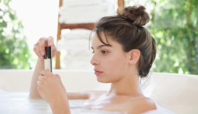 Mujer con su celular en le baño.