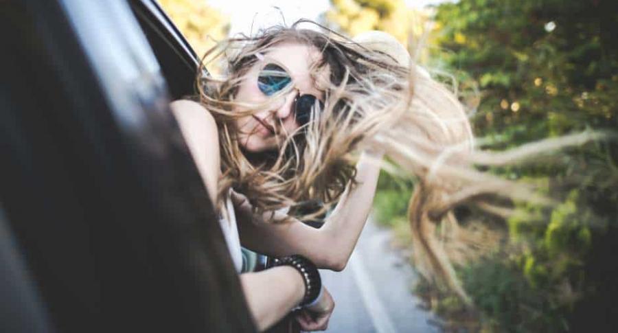 Mujer saca cabeza por ventana de carro.