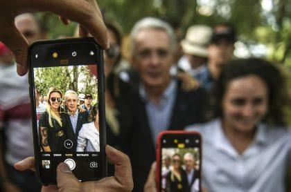 Álvaro Uribe siendo fotografiado con celulares