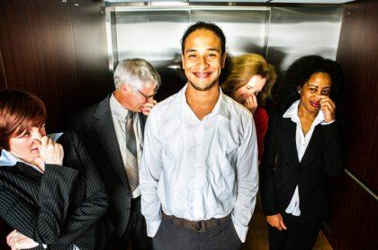 Hombre sonríe después de echarse un pedo en ascensor