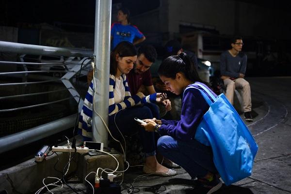 Venezolanos cargando celulares en apagón