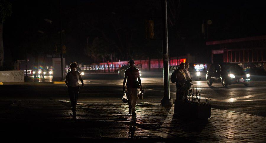 Personas caminan en medio de la oscuridad, en Caracas