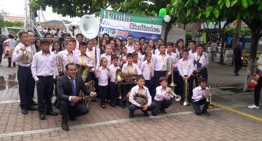 Los niños de la banda sinfónica de Nimaima, junto a su director Alejandro Pinzón.