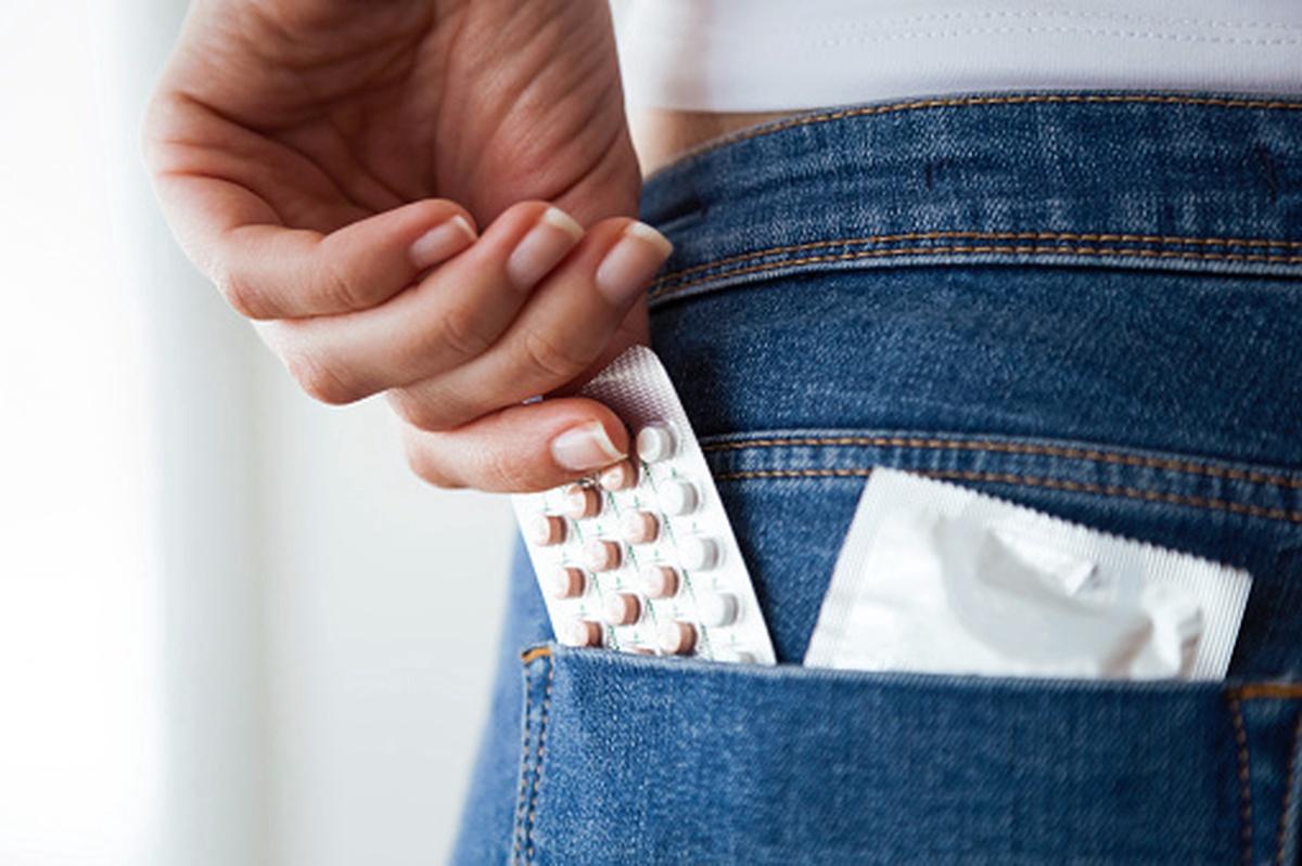 Mujer guardando anticonceptivos en un bolsillo