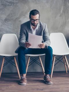 Hombre sentado con hoja en al mano