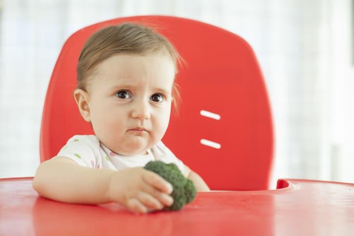 Bebé con brocoli en la mano