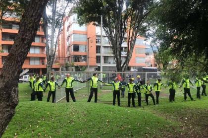 Personas cercando construcción de antena en parque.