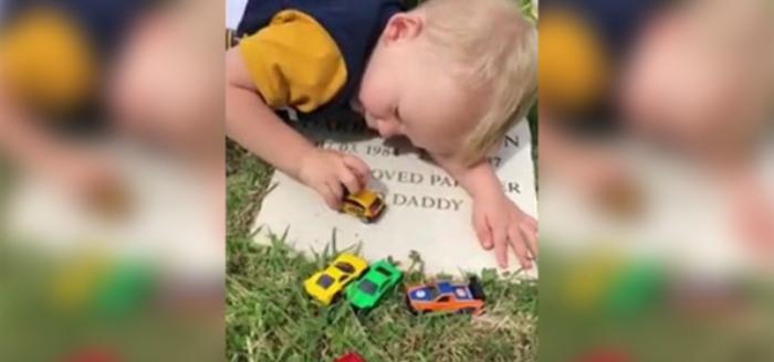 Niño jugando en la tumba de su padre.
