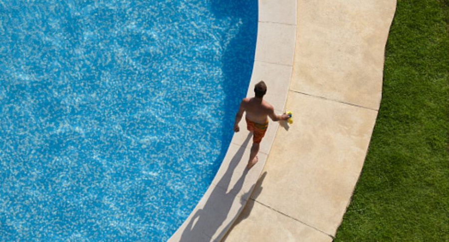 Hombre camina en borde de piscina.