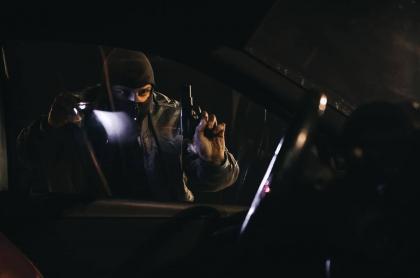 Hombre armado observando un carro.