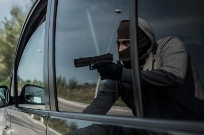 Persona armada abordando un vehículo.