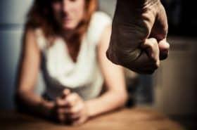Hombre empuñando su mano frente a una mujer. Maltrato a la mujer.