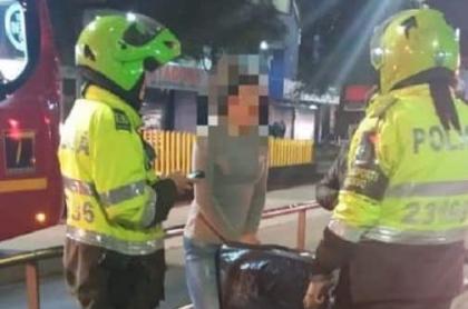 Policías poniendo comparendo a mujer que transportaba lavadora. Imagen: Twitter-Transmilenio