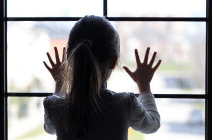 Niña mirando por la ventana.