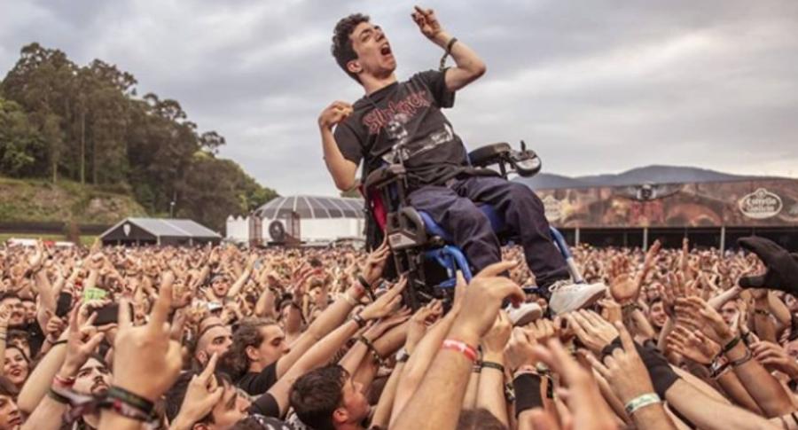 Público alza a hombre en silla de ruedas.