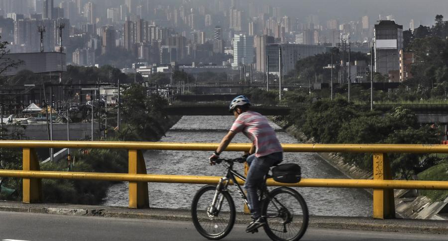 Hombre en bicicleta, y de fondo Medellín