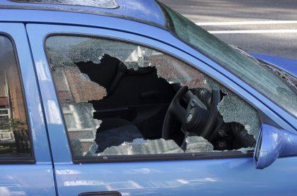 Vehículo azul con los vidrios rotos. Imagen de referencia. Getty.