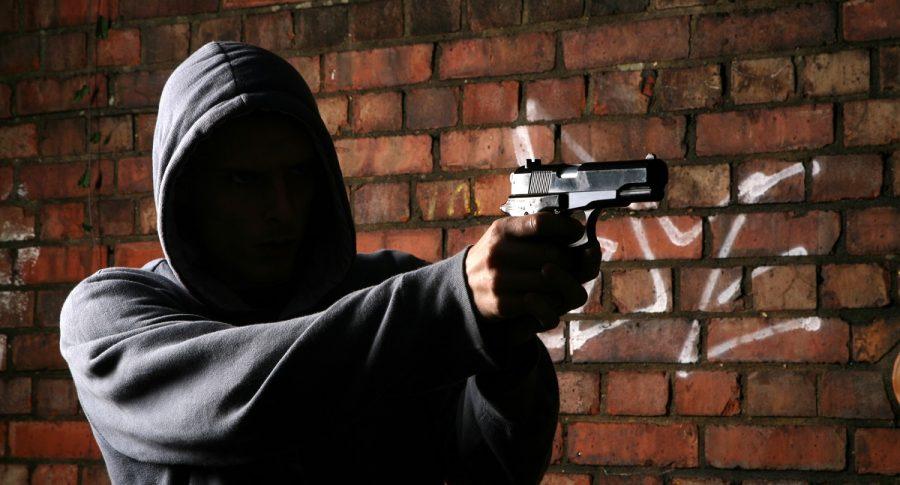 Hombre encapuchado apuntando con un arma. Imagen de referencia Getty.