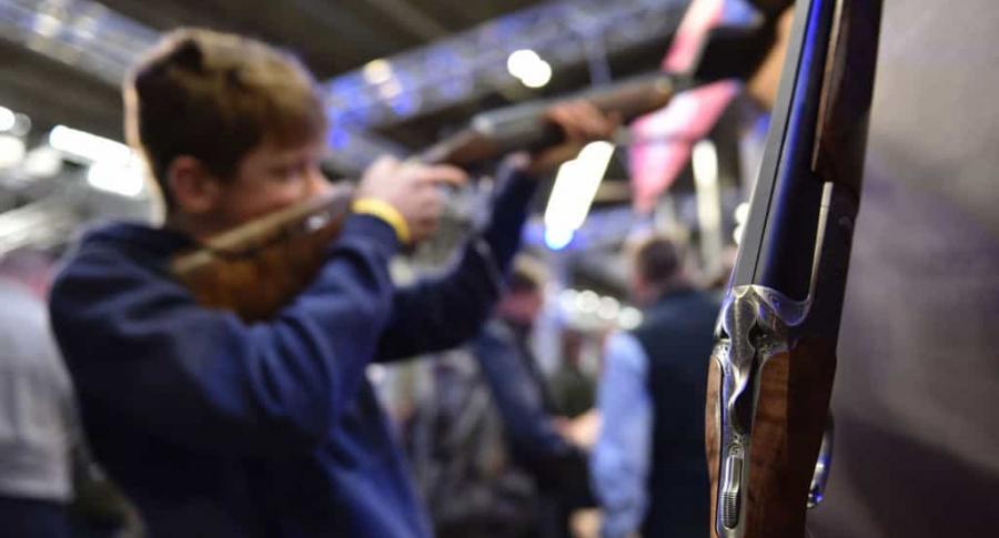 Niño sostiene escopeta armas
