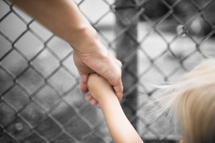 Mujer agarra de mano a niño (manos)