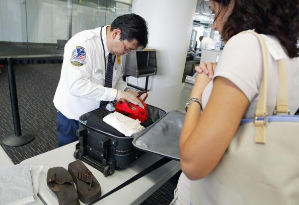 Personal revisando el equipaje de un pasajero