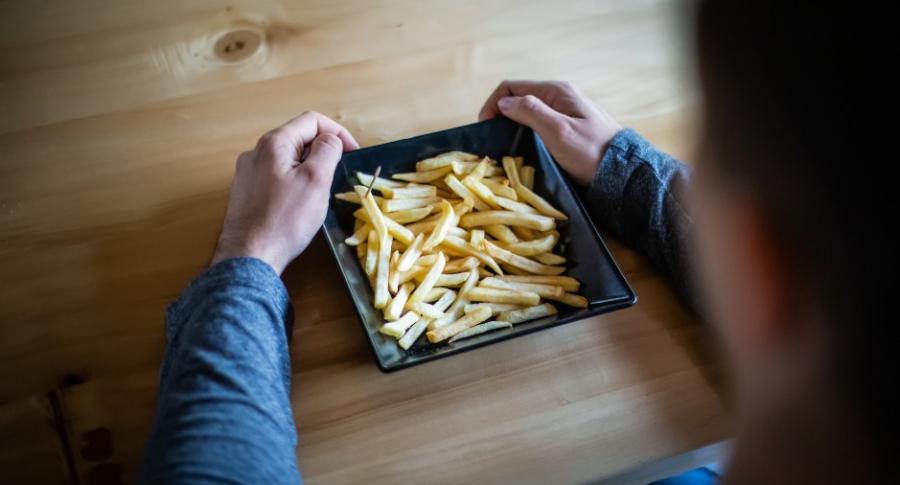 Joven comiendo papas fritas.