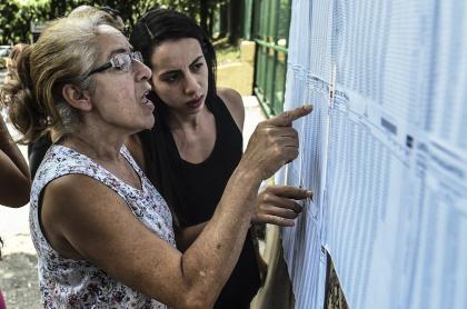 Dos mujeres consultando listas de cédulas