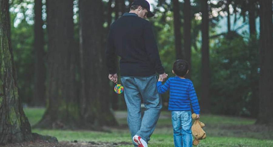Hombre tomando de la mano a niño