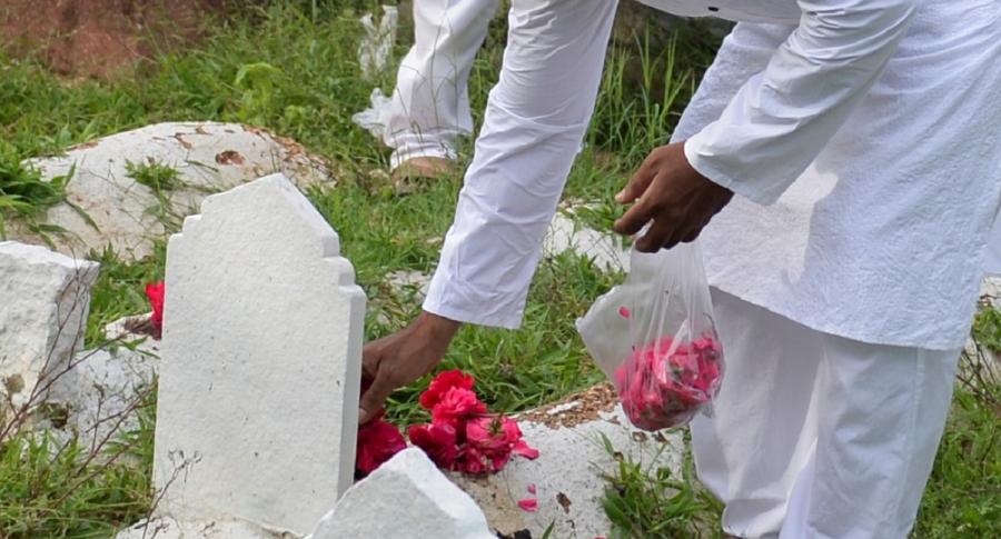 Persona poniendo flores en tumba