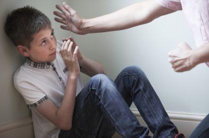 Niño siendo golpeado por adulto