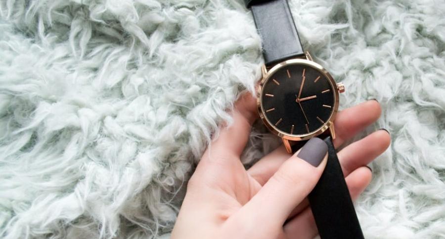 Mujer agarra reloj.