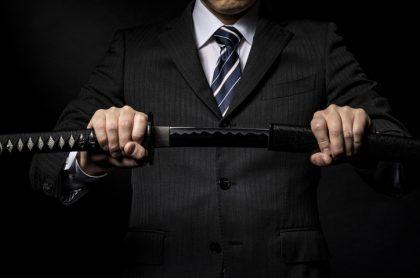 Hombre en traje sostiene espada/sable