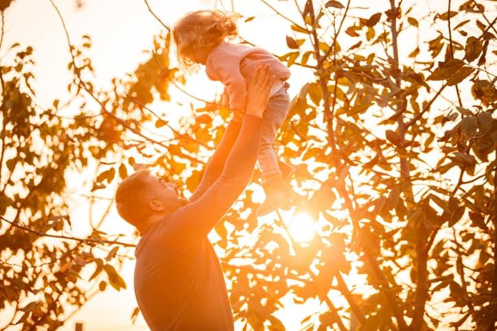 Padre lanzando a su niña en el aire