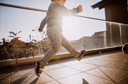 Niño juega en un balcón.