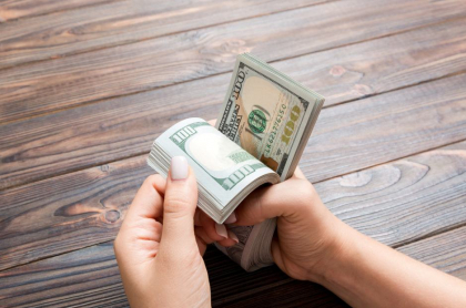 Mujer contando billetes de 100 dólares.