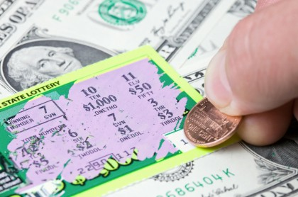 Hombre raspa lotería.