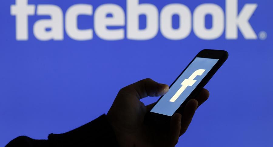 Mano con celular y logo de Facebook