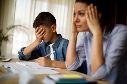Mujer haciendo tareas con el hijo.