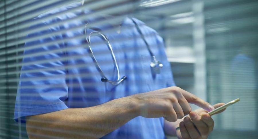 Médico con celular.