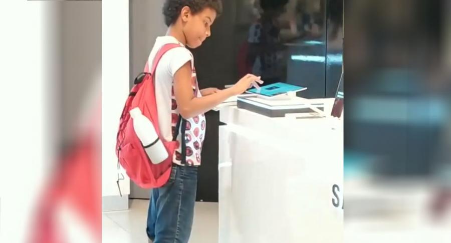 Niño hace tareas en centro comercial.