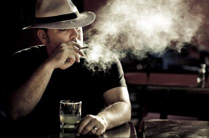 Hombre fumando y bebiendo
