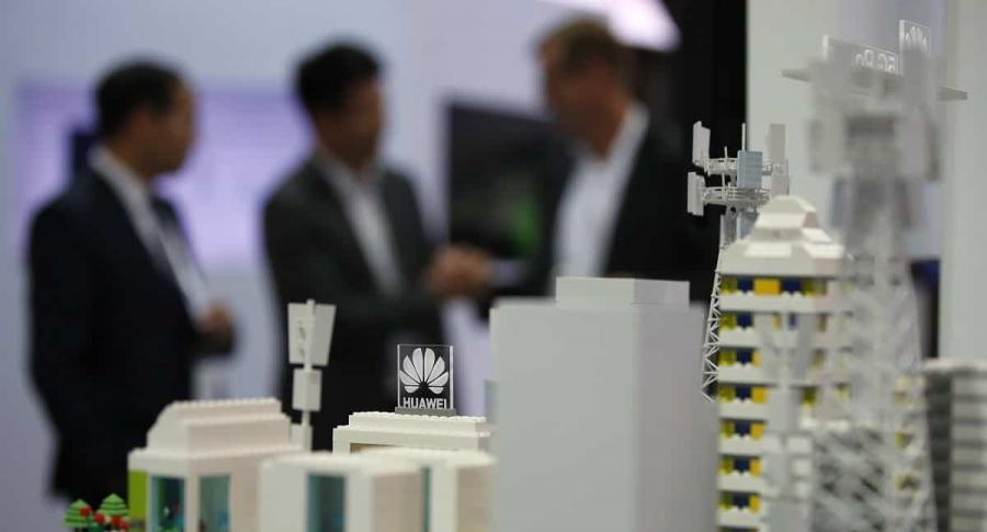 Ejecutivos de Huawei detrás de maqueta con instalaciones tecnológicas