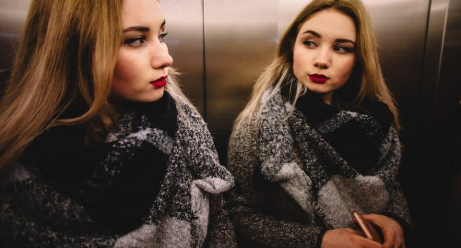 Mujer en ascensor con espejo.