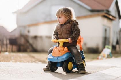 Niño en carro de juguete.