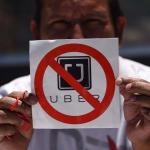 Hombre sostiene cartel de rechazo a Uber