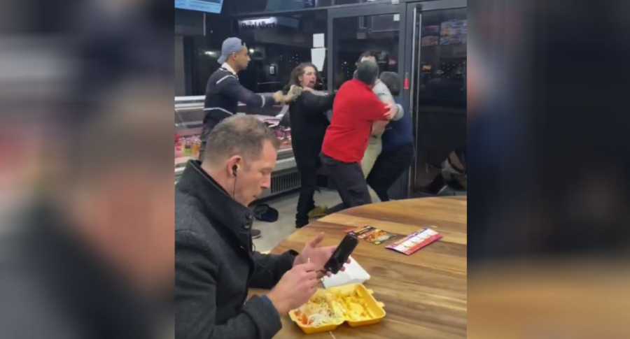 Hombre come mientras presencia pelea.