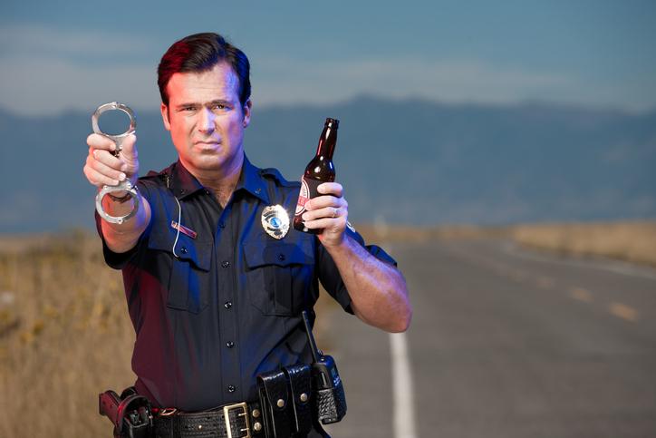 Policía con esposas y cerveza en mano